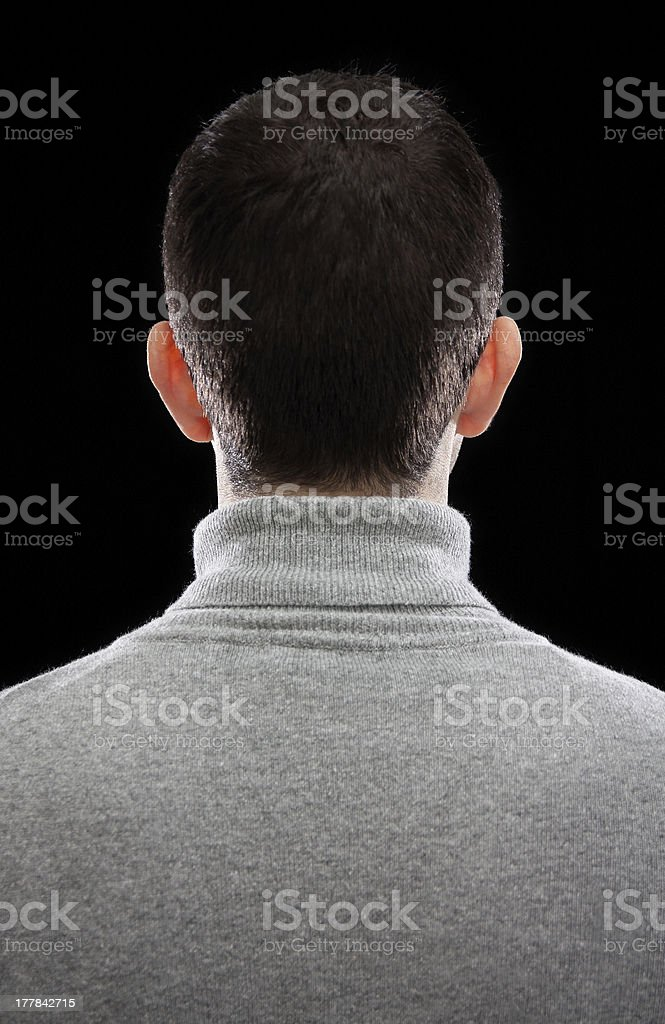 Man with short dark hair and a grey sweater turning his back stock photo