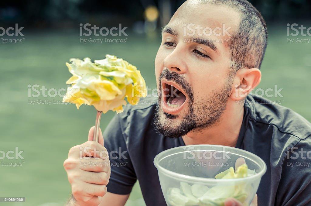 man with short hair and a beard eating salad stock photo