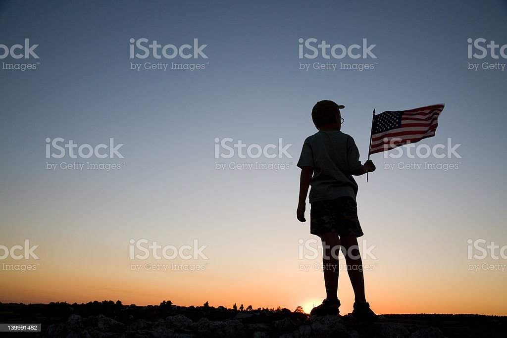 A man with shorts and a t-shirt waving a flag stock photo