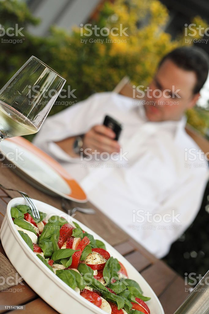 Man with Smart Phone at Dining Table royalty-free stock photo