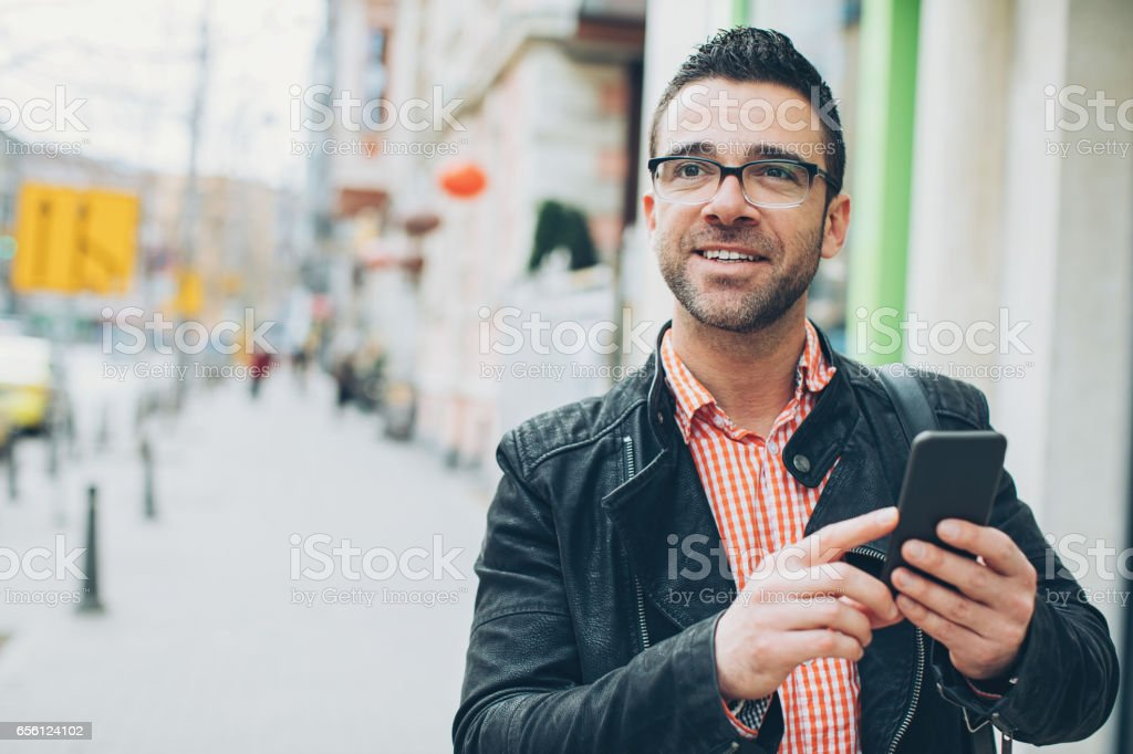 Man with smart phone on the street stock photo