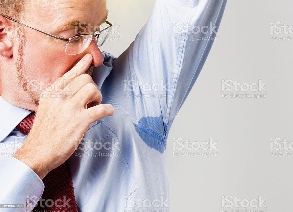 Man with smelly sweaty armpit sniffs at it nervously stock photo