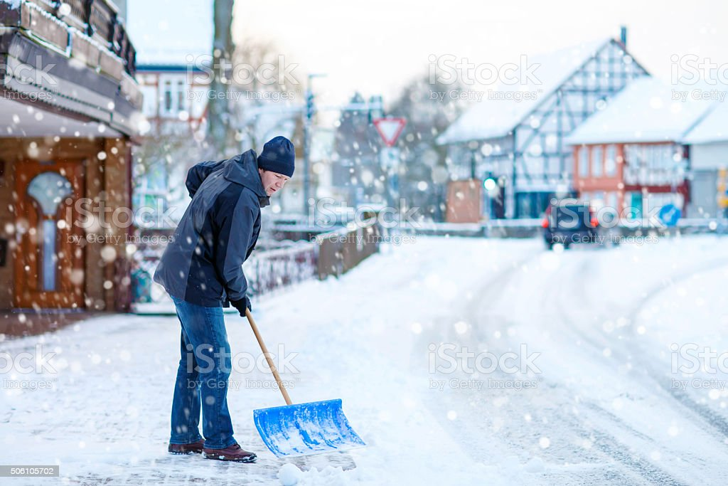 Man with snow shovel cleans sidewalks in winter stock photo