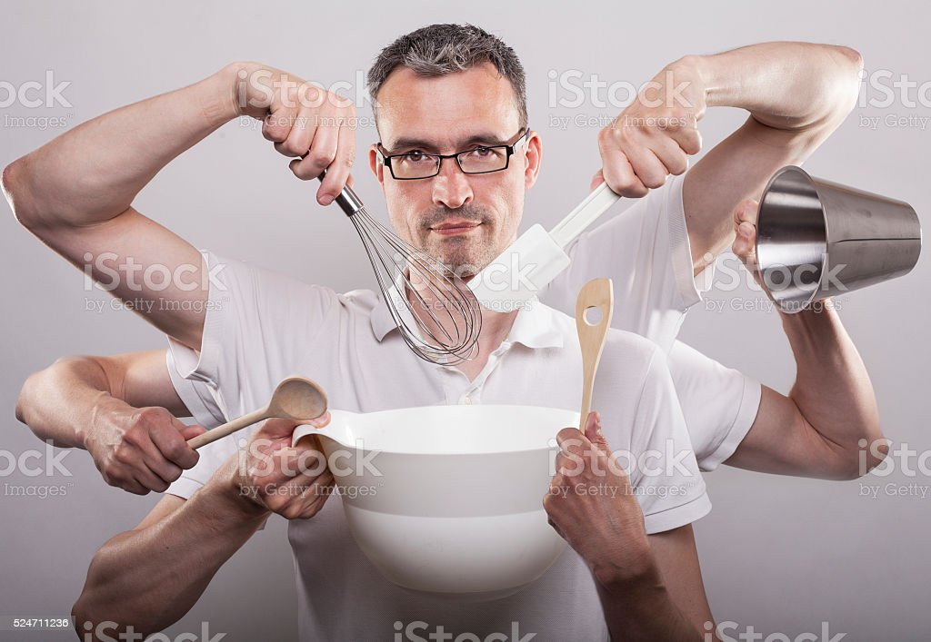 Man with spider arms baking cake stock photo