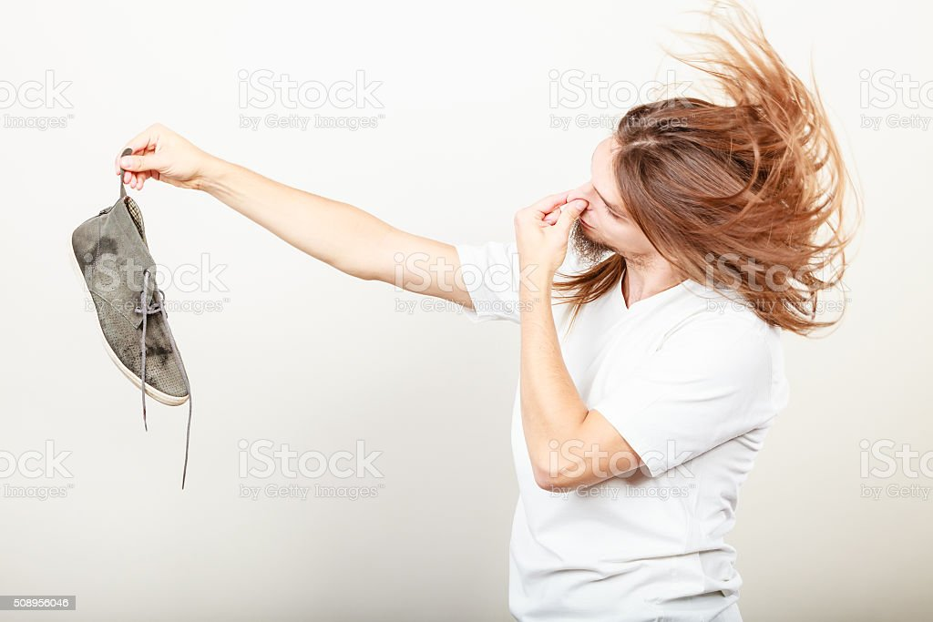 Man with stinky shoe stock photo