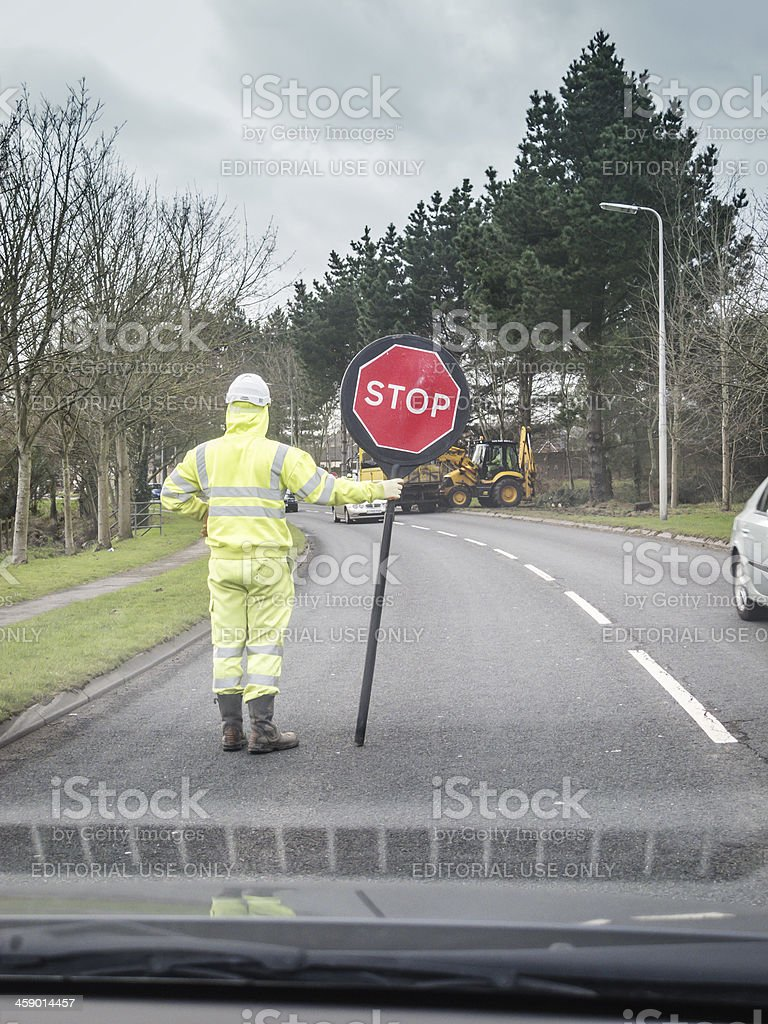 Man with stop sign at rural roadworks royalty-free stock photo