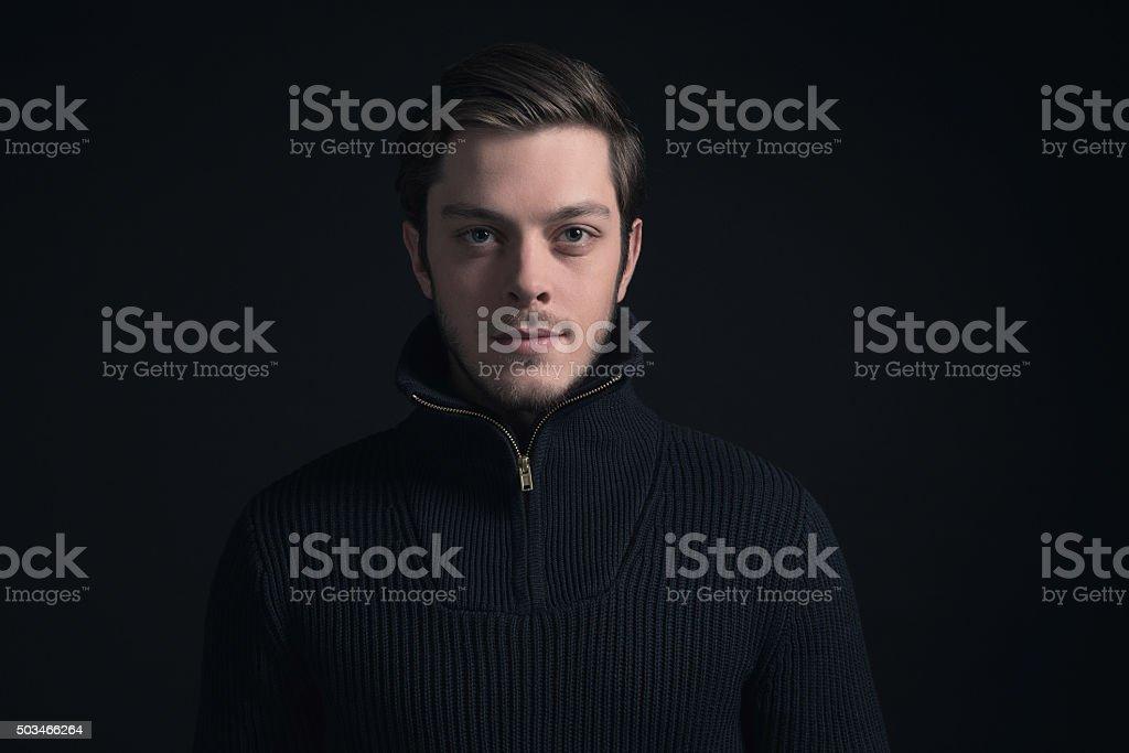 Man with stubbly beard wearing dark blue turtleneck. stock photo