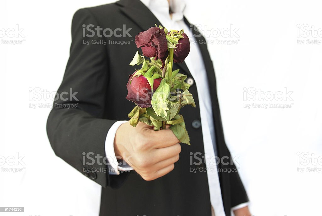 Man with suit holding dead flowers royalty-free stock photo