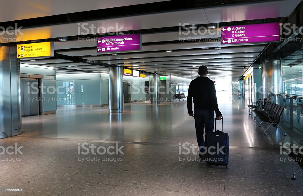 Man with suitcase at an airport lobby. stock photo