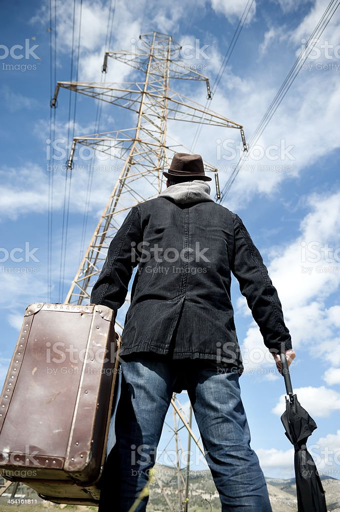 Man with suitcase in a field stock photo