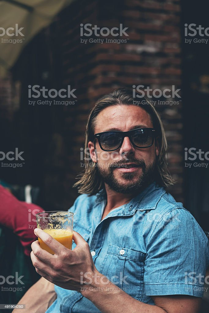 Man with sunglasses drinking fresh juice at an outdoor cafe. stock photo