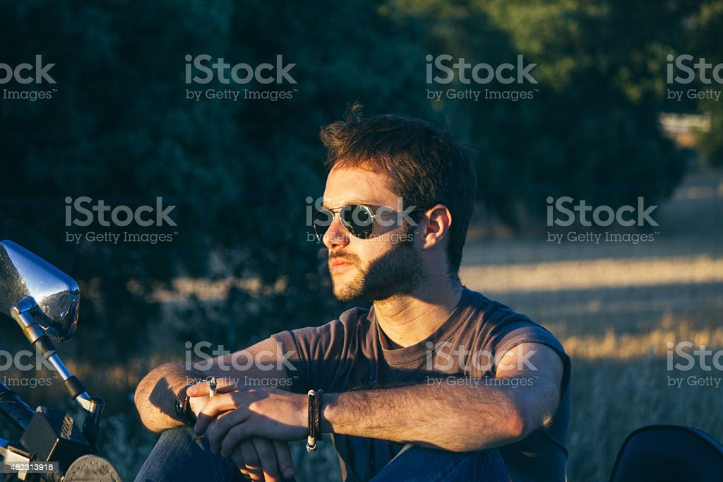 Man with sunglasses sitting on his motorbike at sunset stock photo