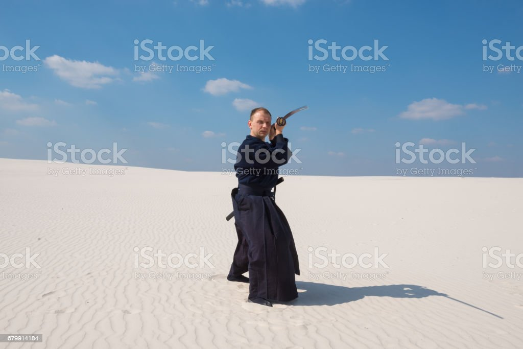 Man with sword in traditional Japanese clothes took the position stock photo