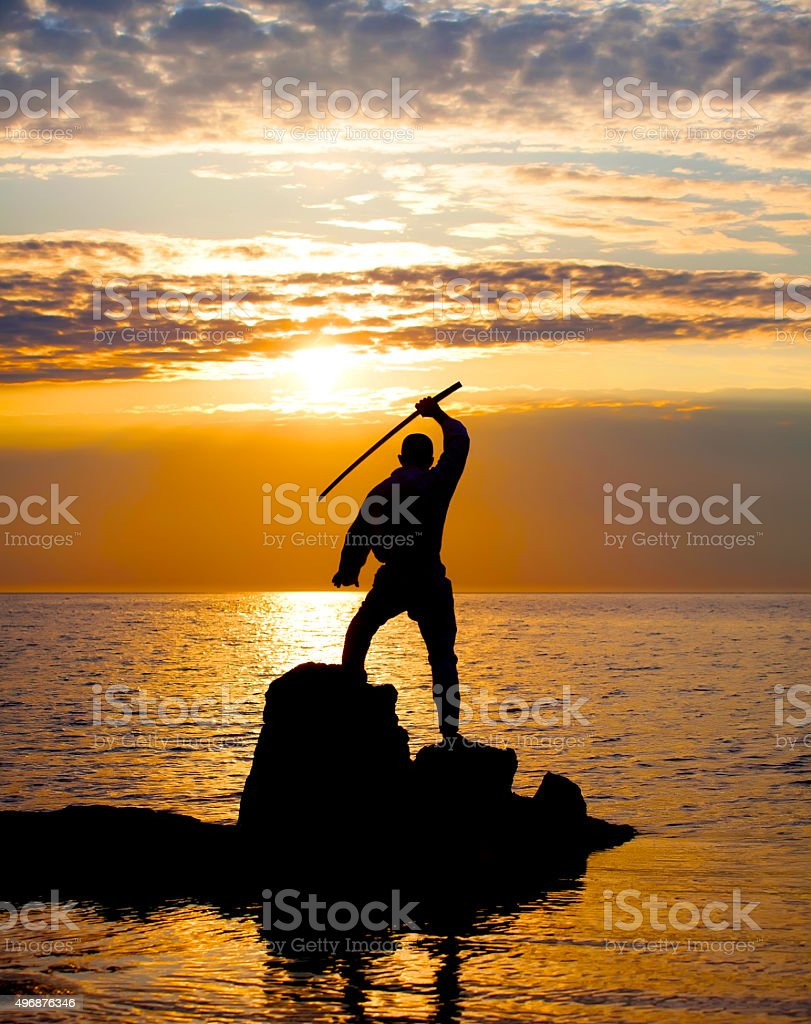 Man with sword on sunset stock photo