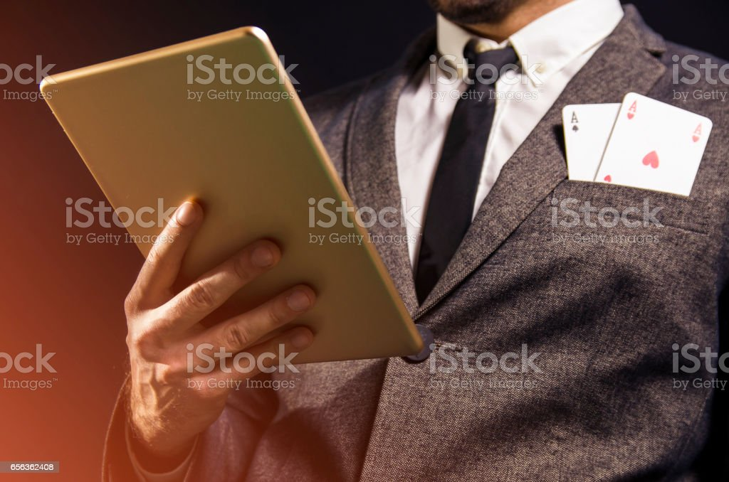 Man with tablet and two aces in pocket / poker concept stock photo