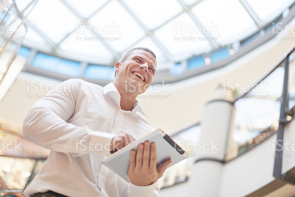Man with tablet computer in modern business building stock photo
