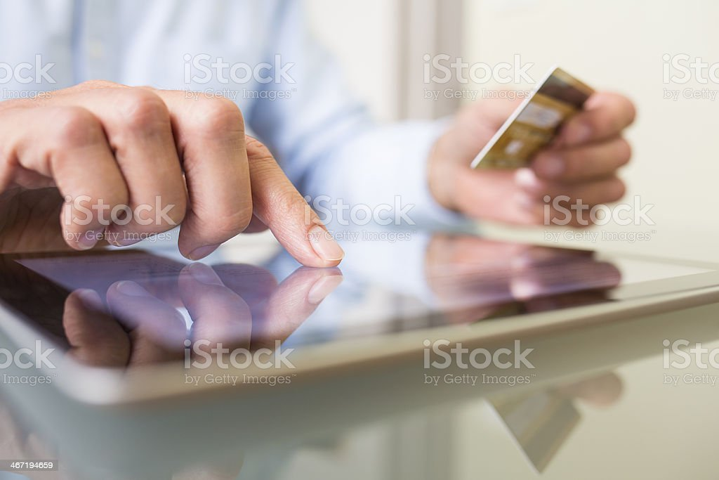 Man using tablet pc and credit card indoor, Shopping online stock photo