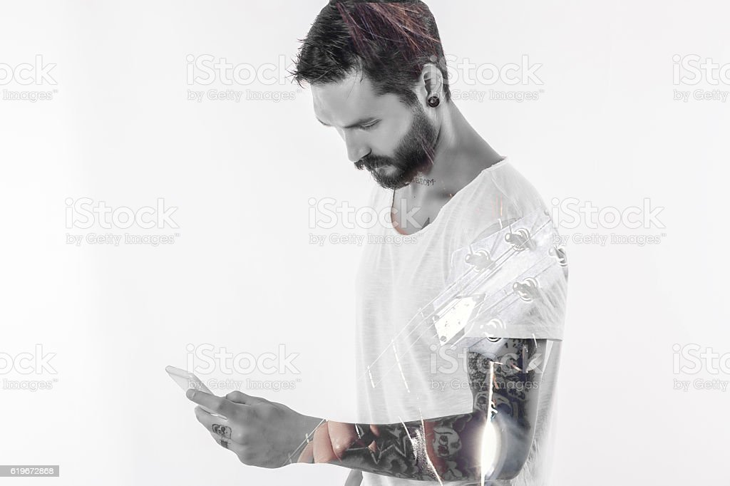 Man with tattoo and phone stock photo