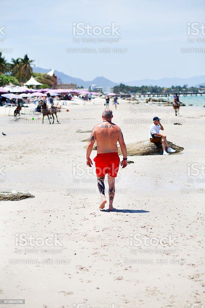 Man with tattoos on beach of Hua Hin stock photo