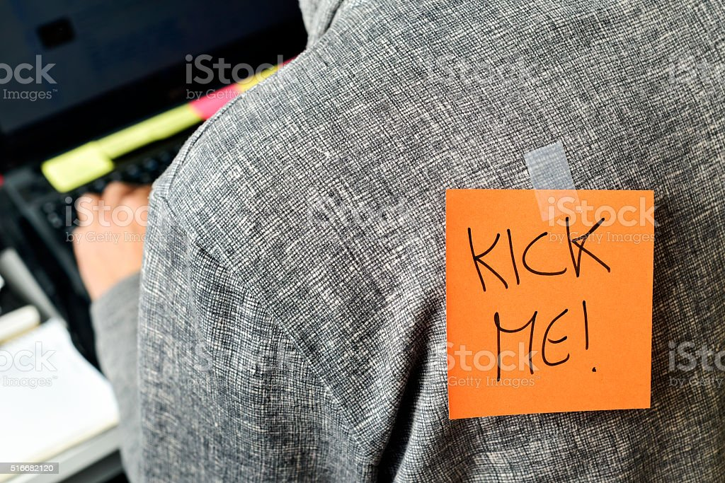 man with text kick me attached to his back stock photo
