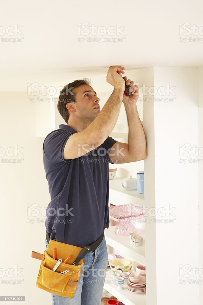 Man with tool belt fixing ceiling pot light royalty-free stock photo