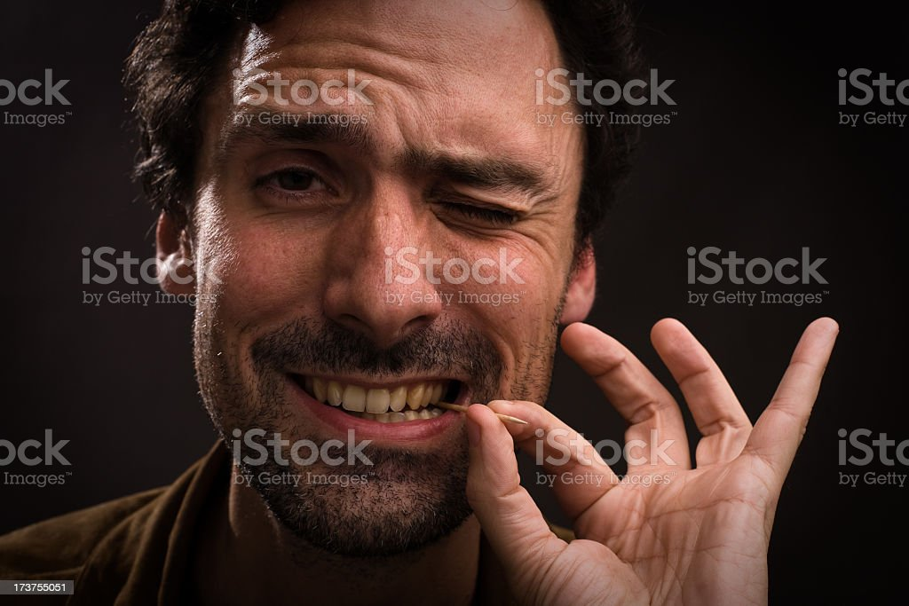Man with toothpick in mouth stock photo
