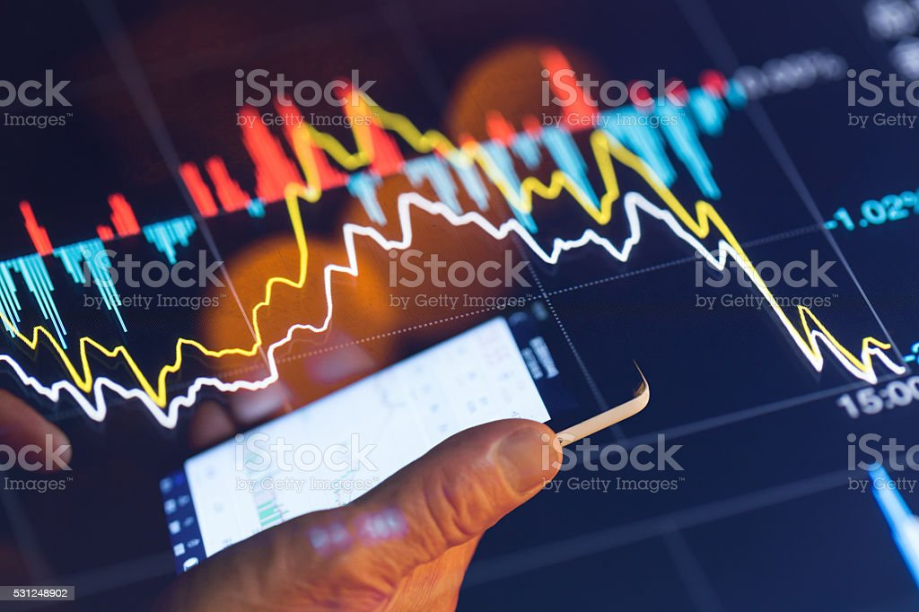 man with touch phone illuminated by stock chart stock photo
