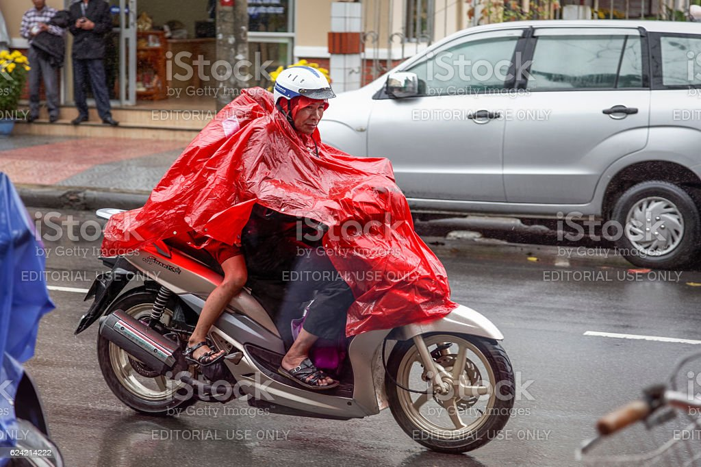 Man with two kids on a motorbike in rain stock photo