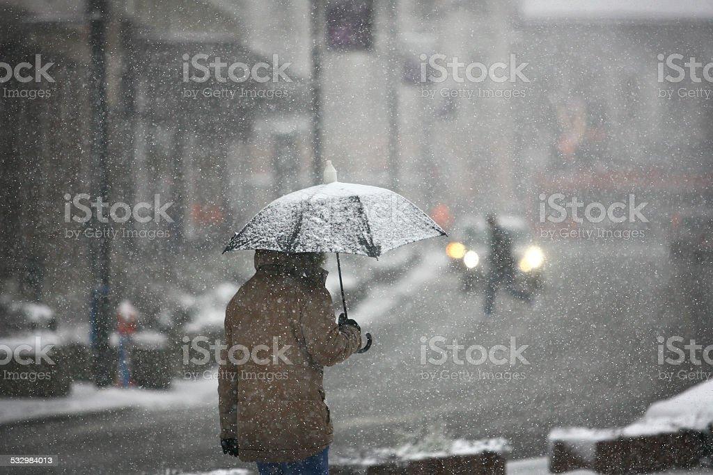 Man with umbrella during snow storm stock photo