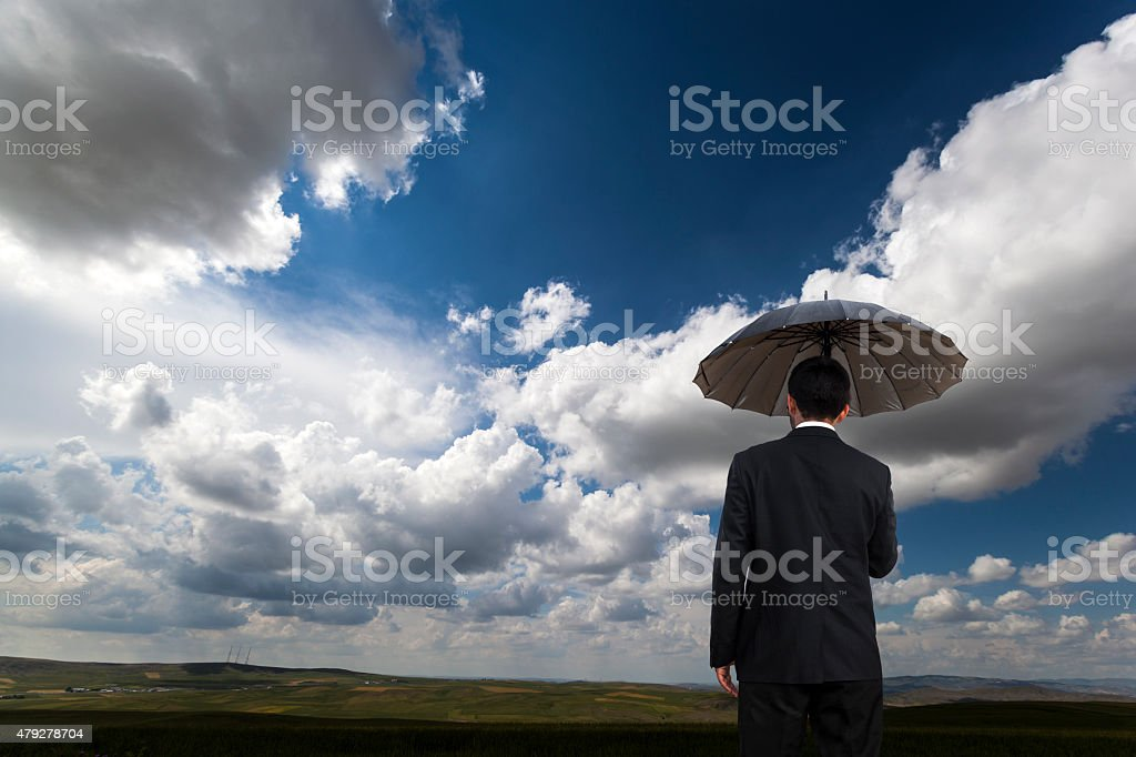 Man with umbrella on Field stock photo