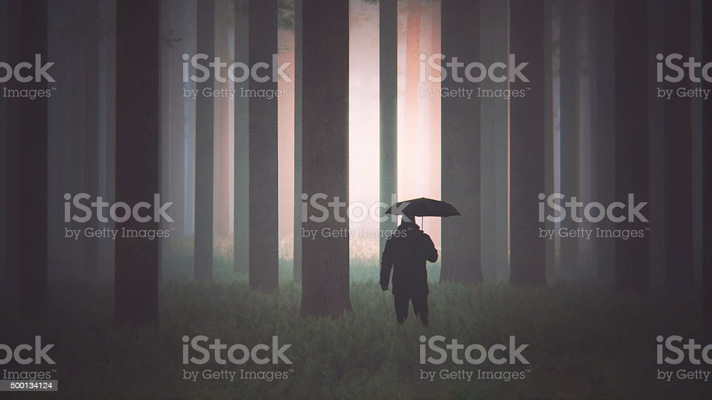 Man with umbrella walking mysterious forest stock photo