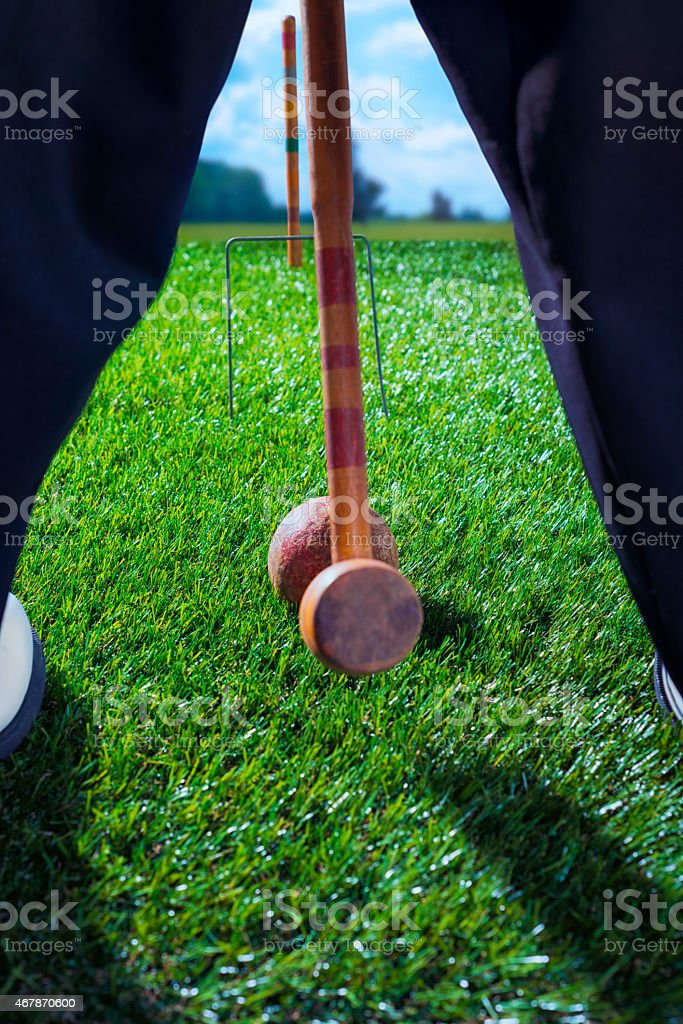 Man with Vintage Croquet mallet about to hit ball stock photo