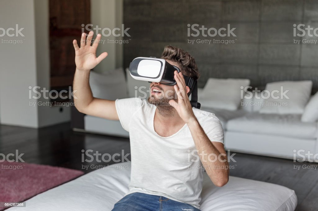 Man with VR headset playing at home in living room stock photo