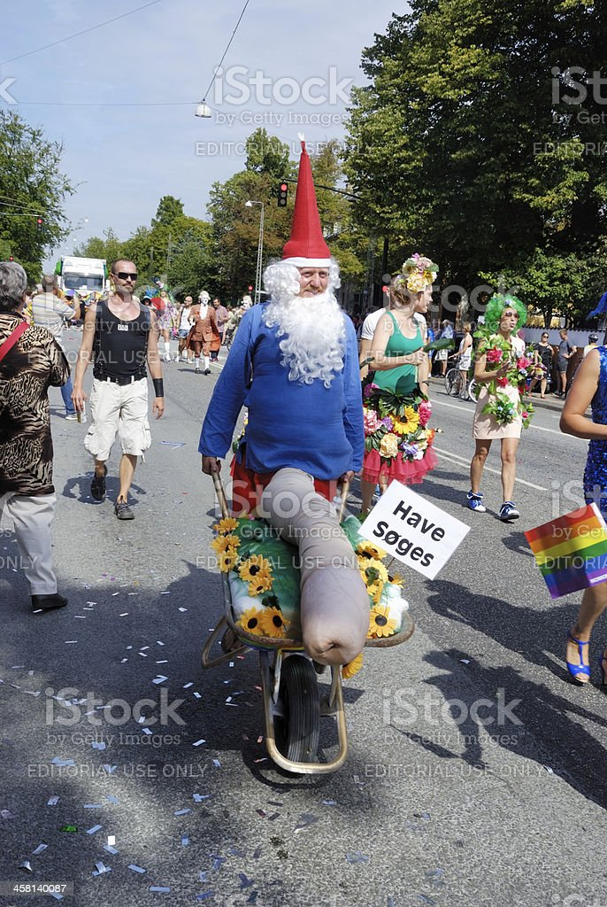 Man with wheelbarrow wearing garden gnome costume royalty-free stock photo