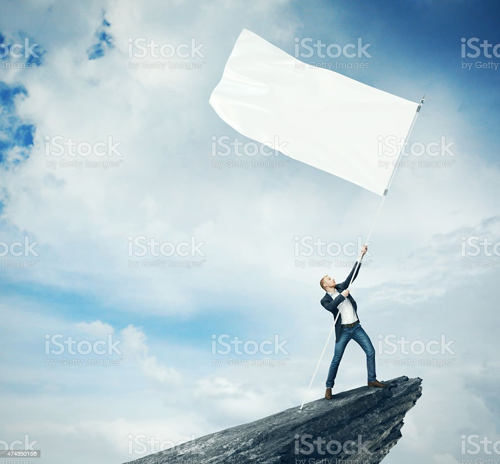Man with white flag standing on a rock stock photo