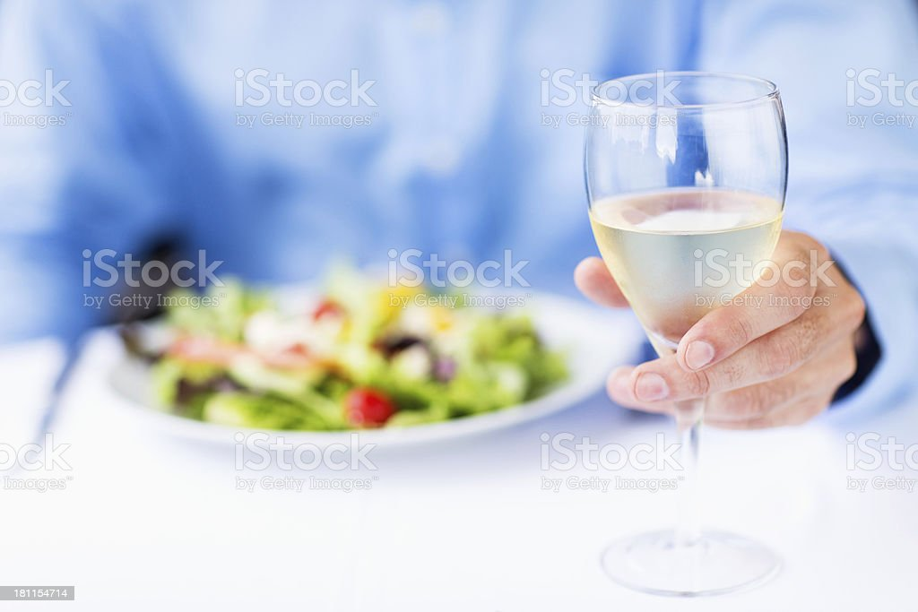 Man With White Wine And Salad Sitting In Restaurant royalty-free stock photo