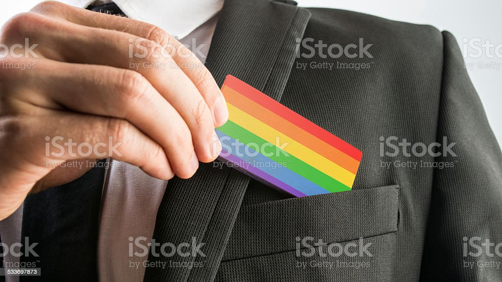 Man withdrawing wooden card painted as the gay pride flag stock photo