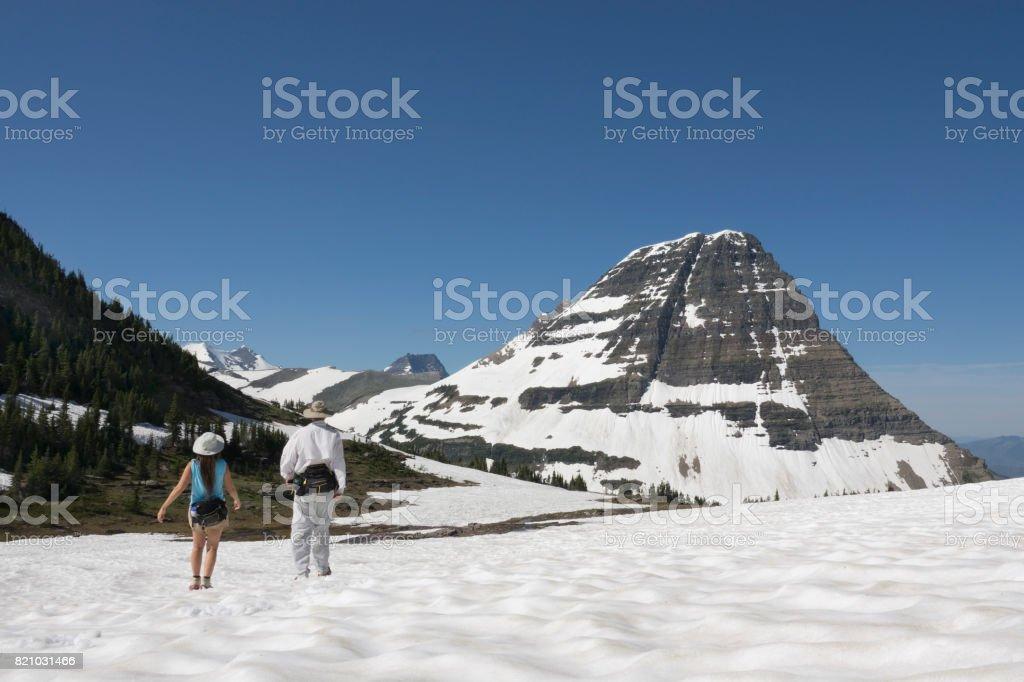Man woman couple hike Glacier National Park Logan Pass snowfield Bearhat Mountain Montana stock photo