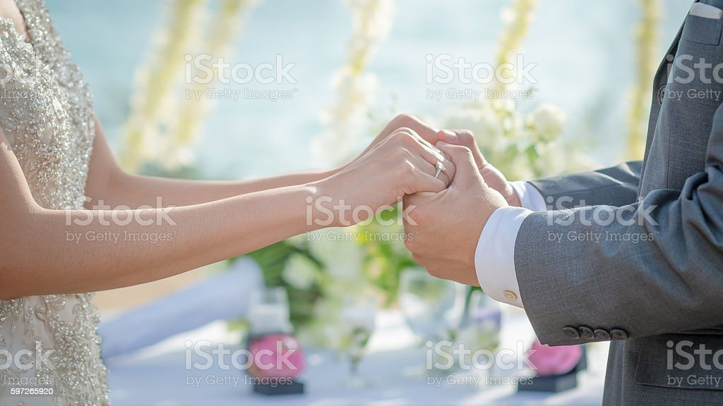 Man & Woman holding hands in wedding ceremony stock photo