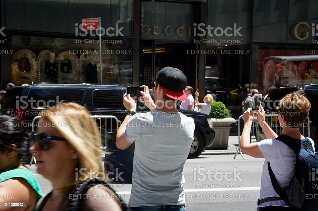Man & woman taking smartphone photos, Midtown Manhattan, NYC stock photo