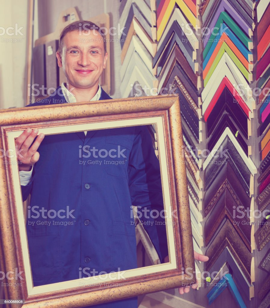 Man worker holding picture frame details on counter stock photo