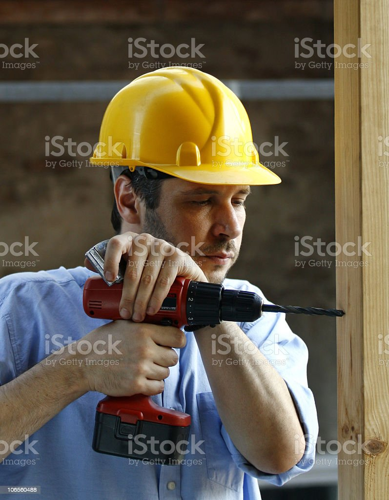 Man worker with hard hat drilling wood royalty-free stock photo