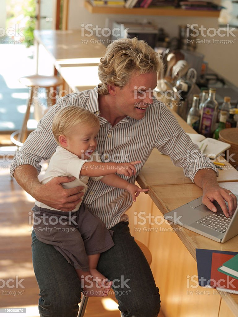 Man working and holding baby son royalty-free stock photo