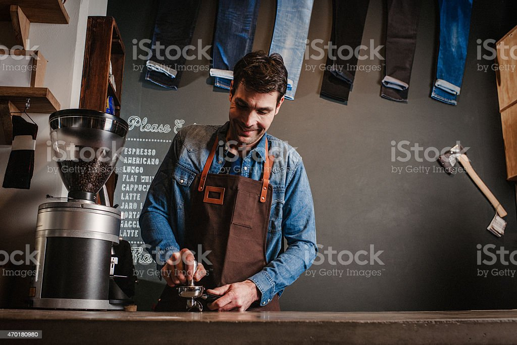 Man working as a barista at a modern coffee shop stock photo