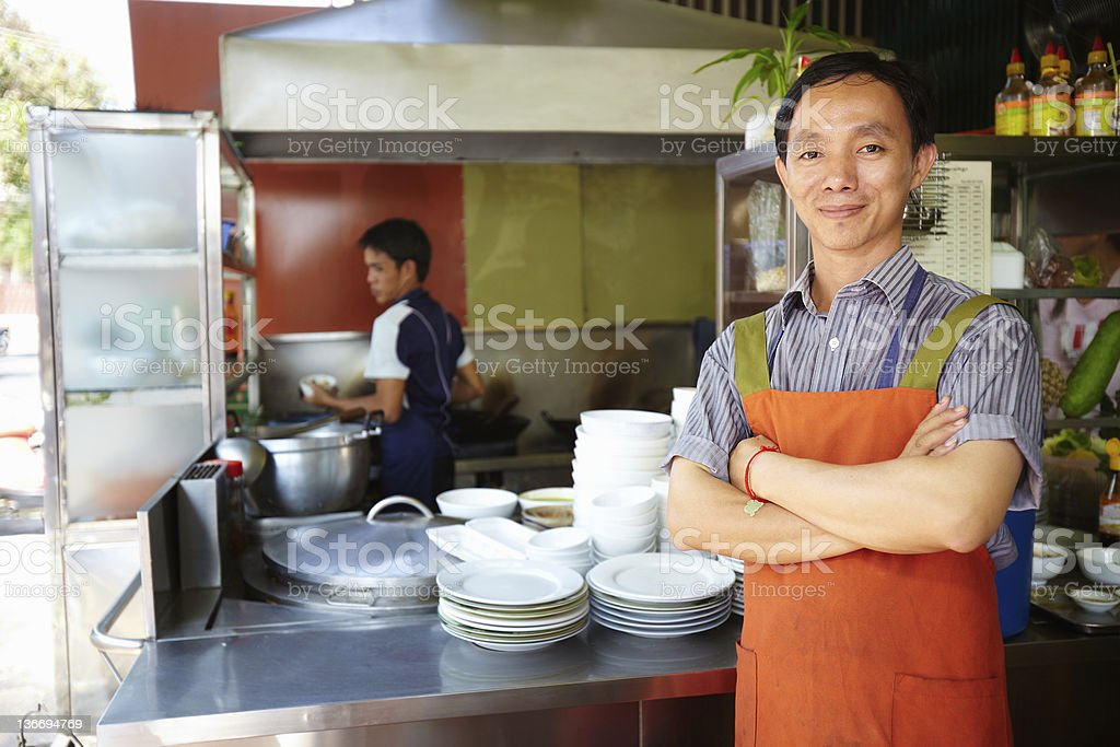 Man working as cook in Asian restaurant kitchen stock photo