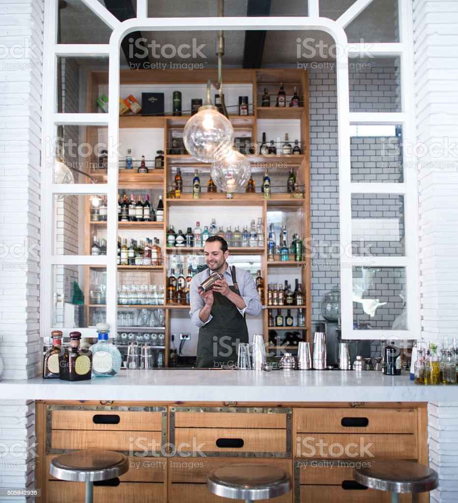 Man working at a bar making cocktails stock photo