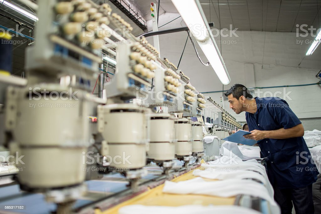 Man working at a clothing factory stock photo