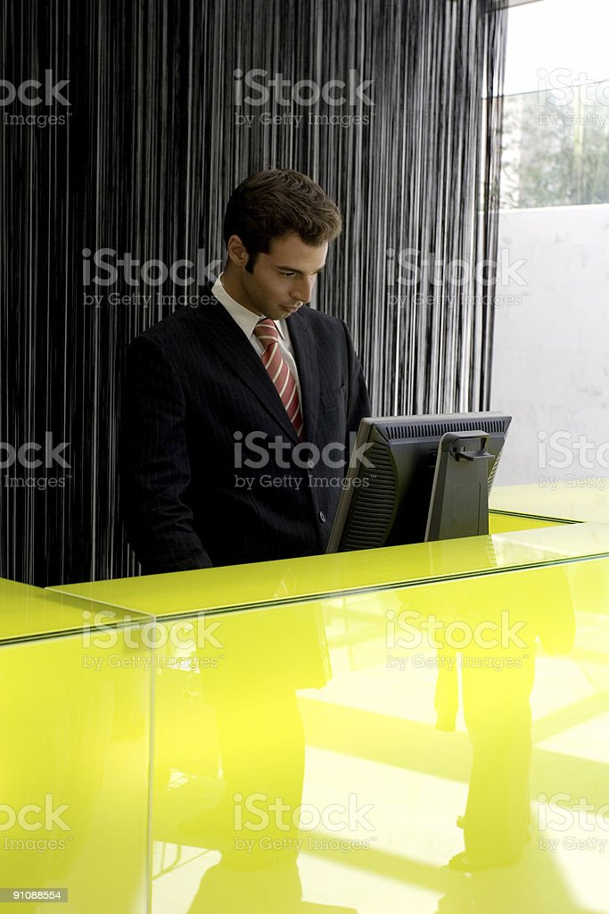 Man working at a front desk doing check ins royalty-free stock photo