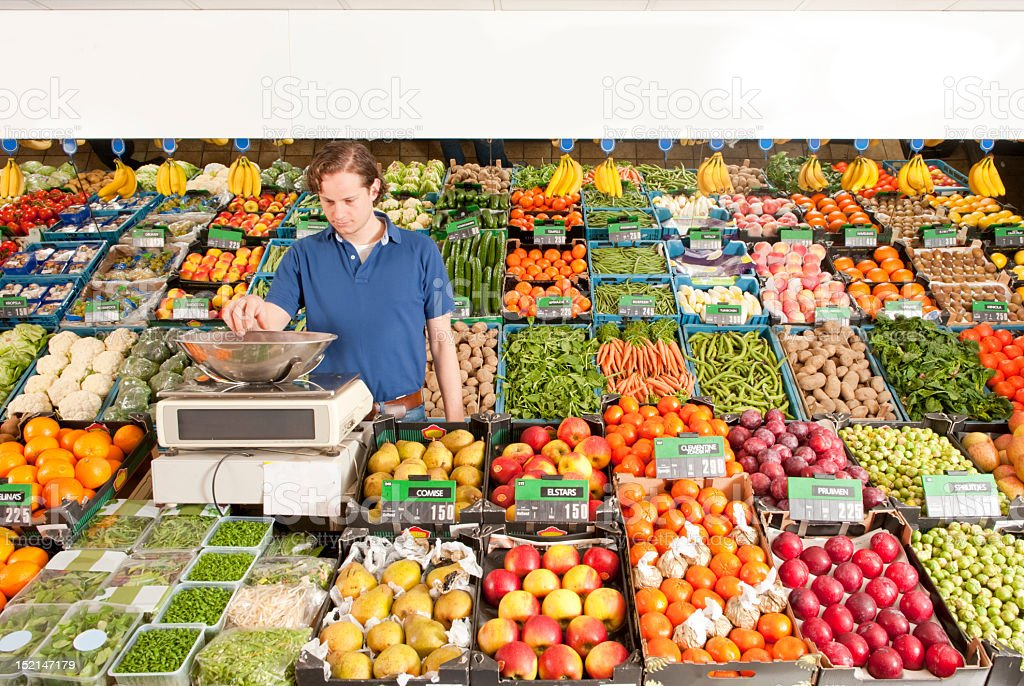 A man working at a green grocery store weighing vegetables stock photo