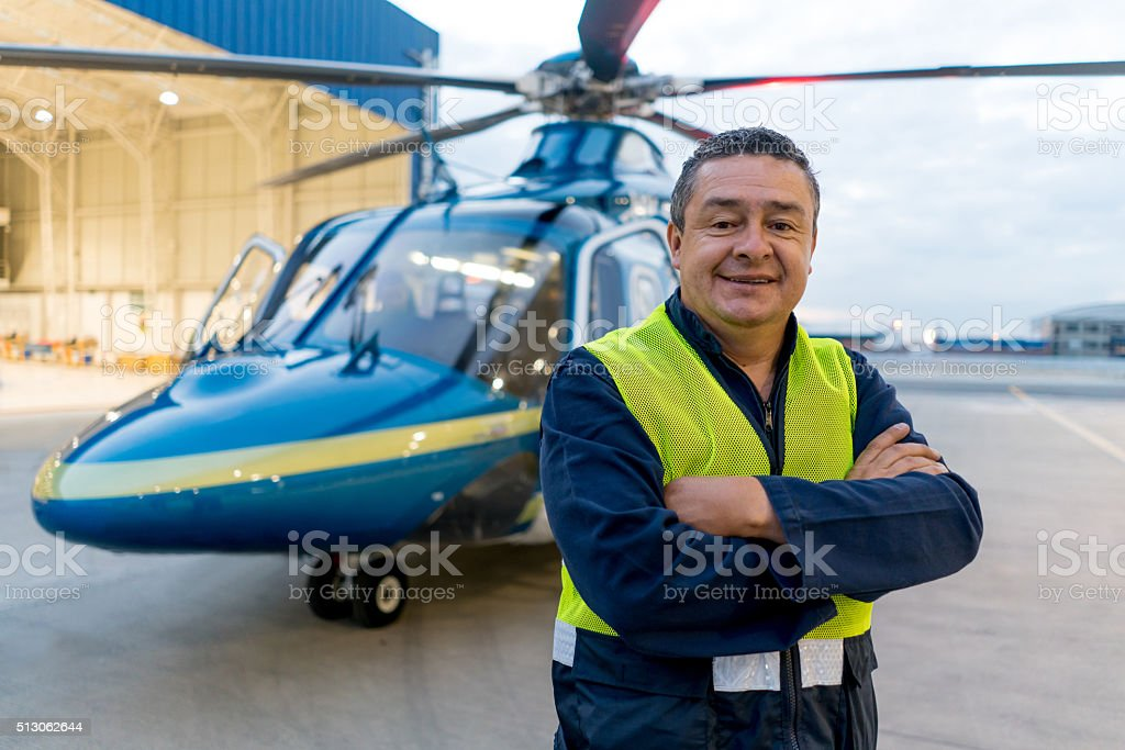 Man working at a helicopter hangar stock photo